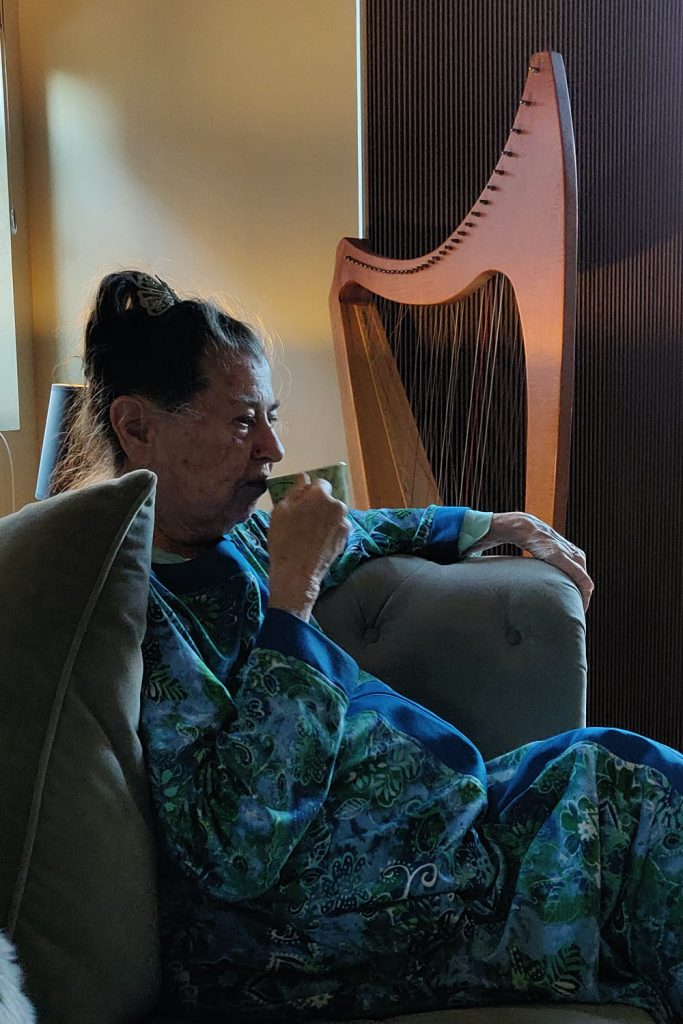 Mrs Walley in robe enjoying a cup of coffee next to her harp. April 28, 2020. Photo copyright © Reid Walley